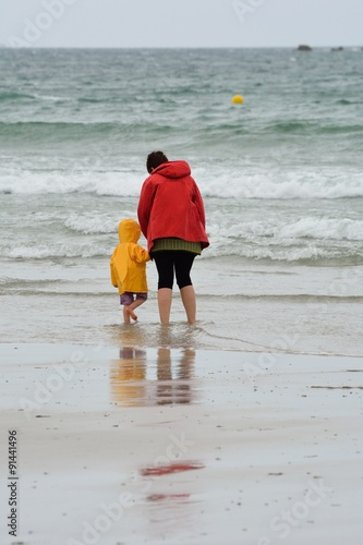 Photo  Une dame et un enfant sur une plage près de l'eau par temps pluvieux