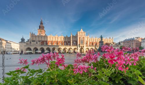 Fototapeta Cloth hall on the main market square in Krakow, Poland, with geranium flowers during golden hour obraz