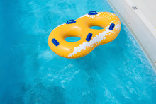 Yellow Rubber Ring Floating On Refreshing Blue Water