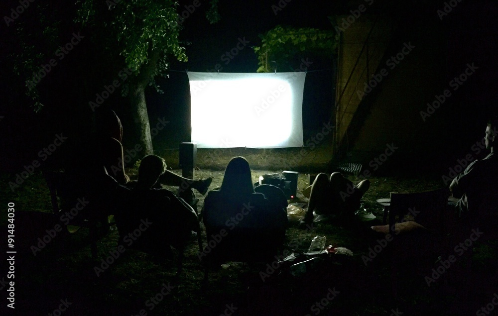 Fototapety, obrazy: Friends watching movie outside in the yard