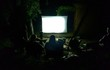 Friends watching movie outside in the yard
