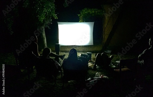 Foto  Friends watching movie outside in the yard