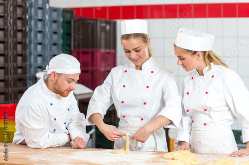 apprentice in bakery trying to make pretzels and sceptical bakers watching