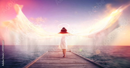 Foto  Female angel on a jetty overlooking the ocean