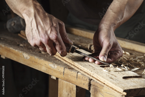 carpenter hands working with a chisel and carving tools Fototapeta