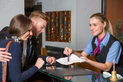 Plakat recepcjonista w hotelu pokazujący gościom coś na mapie