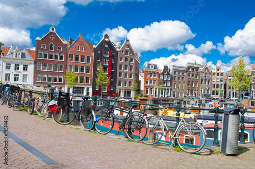 Photo  Amsterdam, the Netherlands-April 27: Amsterdam cityscape with apartment houses and bikes parked on the bridge on April 27,2015