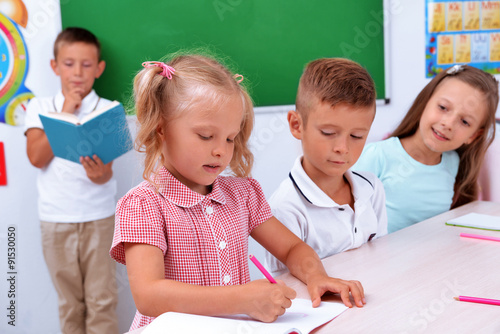 Fototapety, obrazy: Group of children at the desk in classroom