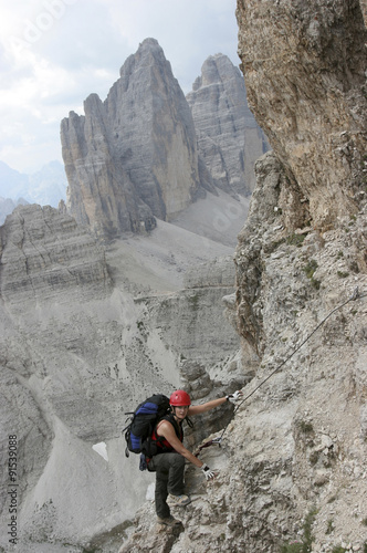 Foto op Plexiglas Alpinisme Frau am Klettersteig auf den Paternkofel, Sextener Dolomiten, im Hintergrund die Drei Zinnen