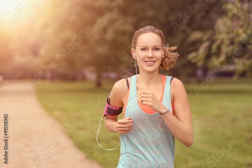 Poster Jogging Hübsche Frau macht Jogging im Park mit Smartphone