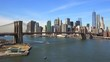 Nice establishing shot of New York City financial district with Brooklyn Bridge foreground and boats passing under.