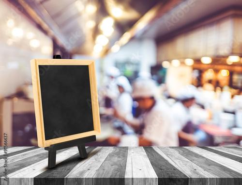 Fototapeta Blackboard menu with easel on wooden table with blur open kitche obraz na płótnie