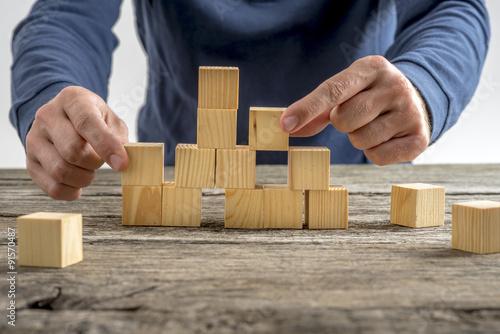 Fotografía  Man Assembling Wooden Cubes on Table