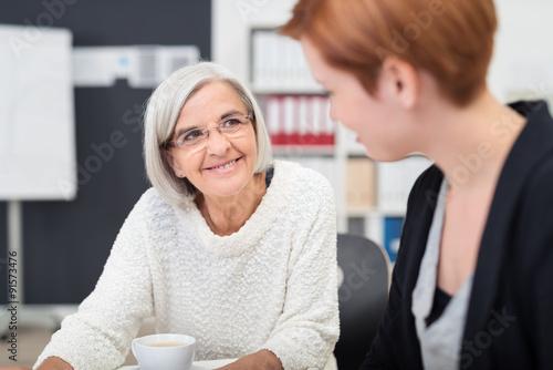Fotografie, Obraz  zwei lächelnde kolleginnen verschiedenen alters unterhalten sich am arbeitsplatz