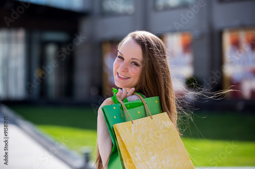Photo  Smiling beautiful young woman with colorful shopping bags standing at the shoppi