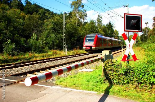 Fotografia, Obraz  Zug nähert sich einem Bahnübergang mit geschlossener Schranke