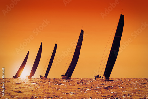 obraz dibond sailing yachts at sunset on the sea