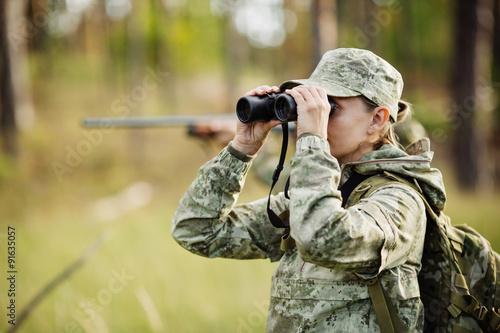 Photographie hunter with shotgun looking through binoculars in forest