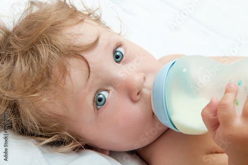 Vászonkép little curly-headed baby sucks a bottle of milk