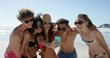 Mixed race group of friends taking selfies on the beach using phone camera