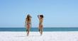 Sexy beach girls wearing bikinis walking towards sea on tropical beach vacation
