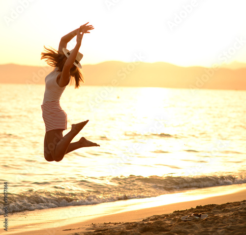 Fotografie, Tablou  Happy Woman Jumping in Sea Sunset