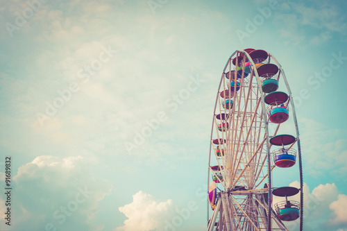 Foto op Canvas Carnaval Ferris wheel on cloudy sky background vintage color