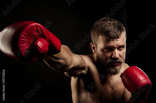Photographie  Athletic bearded boxer with gloves on a dark background