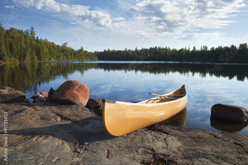 Yellow canoe on rocky shore of calm lake with pine trees Canvas Print