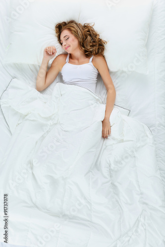 Photo  Shot of a young woman sleeping on a bed .