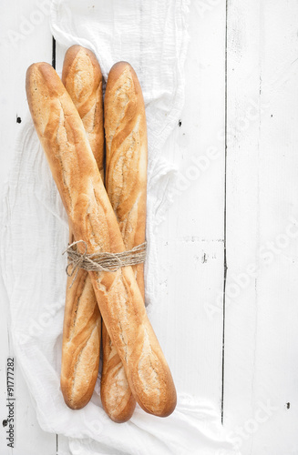 Fotografia, Obraz  Freshly baked French baguettes on white wooden table. Top view