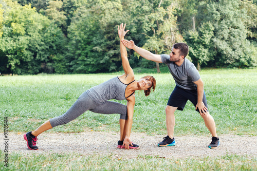 Personal trainer helps a woman during exercise