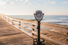 Coing-Operating Sightseeing Binoculars With Beach Background On The Virginia Beach Fishing Pier