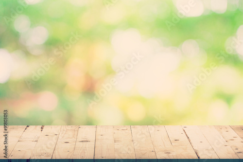 Poster Bois Green leaf bokeh blur and wood table for natural background