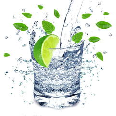Fototapeta Do gastronomi water splash in a glass with lime and mint isolated on white background