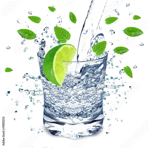 Poster Eclaboussures d eau water splash in a glass with lime and mint isolated on white background