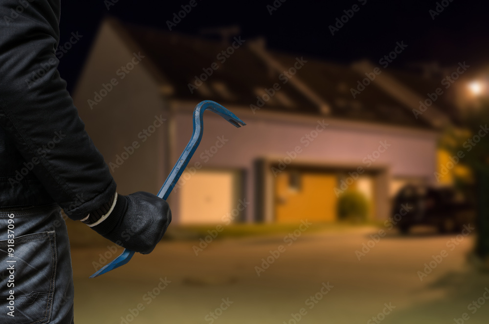 Fototapeta Crime concept. Burglar or robber with crowbar stands in front of