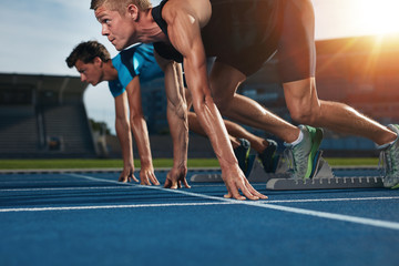 Fototapeta Fit athlete running race in athletics racetrack on a sunny day