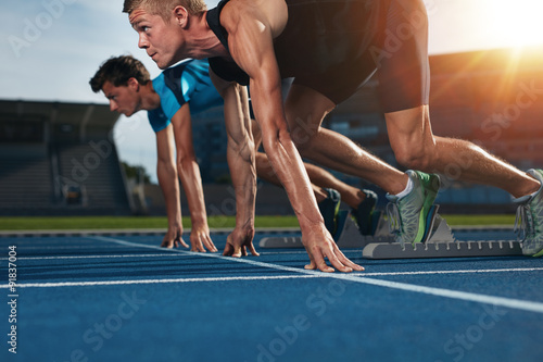 Fotografie, Obraz  Fit athlete running race in athletics racetrack on a sunny day