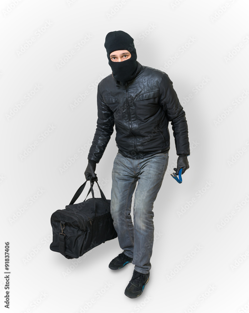 Fototapeta Masked burglar or thief with balaclava is sneaking with black ba