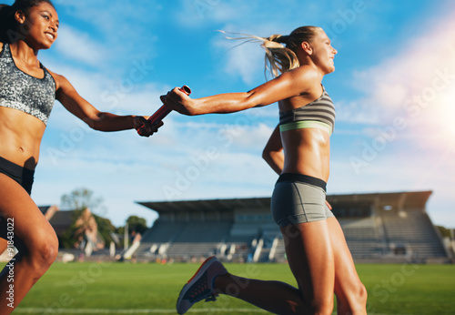 Fotografia  Female relay team passing the baton