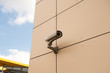 White security camera devices on light gray building.
