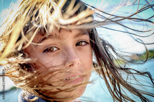 Fényképezés  Portrait of a beautiful eight year old girl with the wind blowin