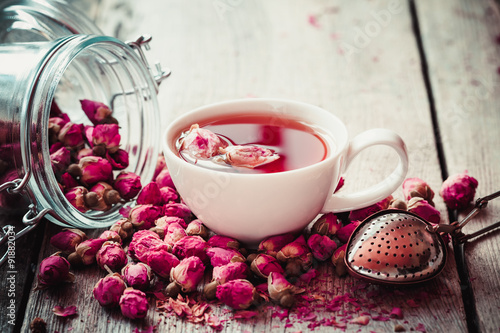 Fotografia, Obraz  Rose buds tea, tea cup, strainer and glass jar with rosebuds. Se