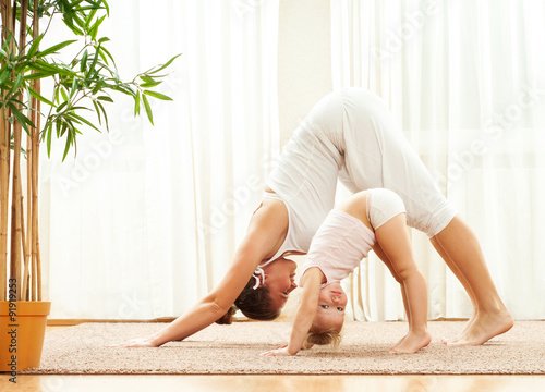 Tuinposter School de yoga Mother and daughter doing yoga exercise home. Mother and baby g