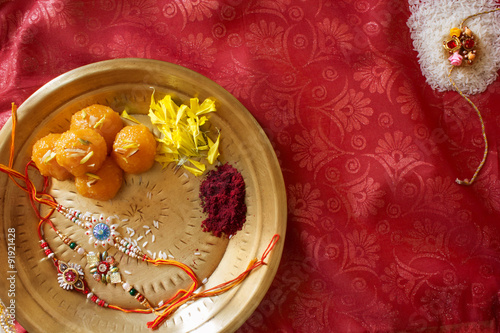 Fotografering  Top View of a plate containing Rakhi and ladoo with sindoor and some flowers marking the religious celebration of Raksha Bhandan