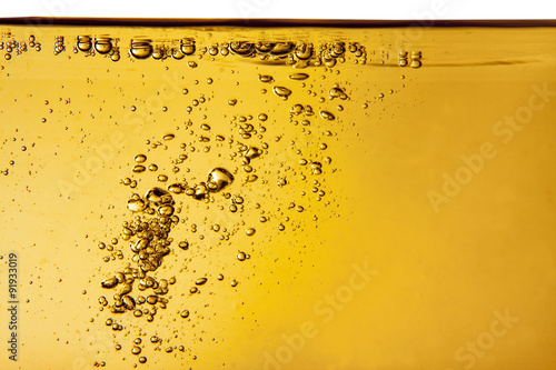 Leinwand Poster Yellow liquid with bubbles