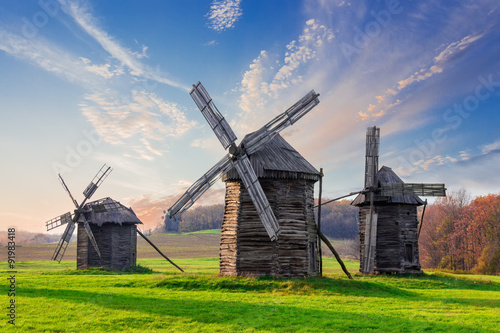 Old windmills on a background of forest and sky