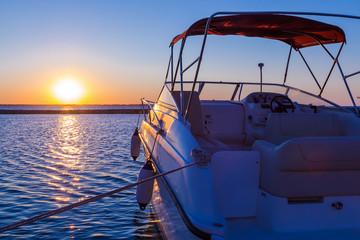Fototapeta na wymiar Yacht near the pier against sunset