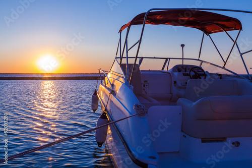 Obrazy na płótnie Canvas Yacht near the pier against sunset